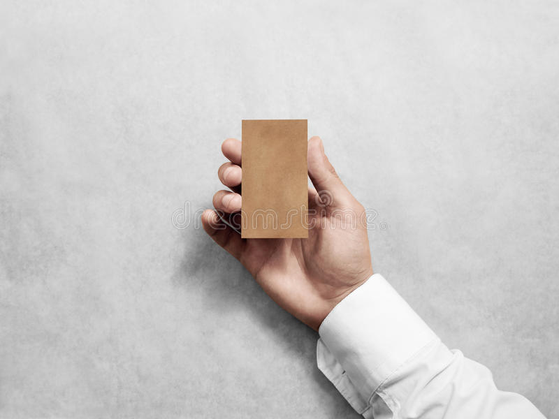Hand hold blank vertical craft business card design mockup. Brown calling card mock up template holding arm. Visit pasteboard kraft paper display front. Small stock photo
