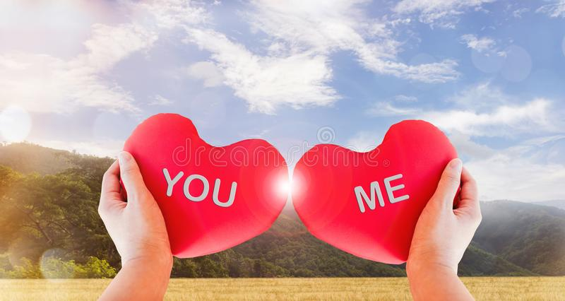 Hand hold couple red heart with text you and me on nature background stock photo