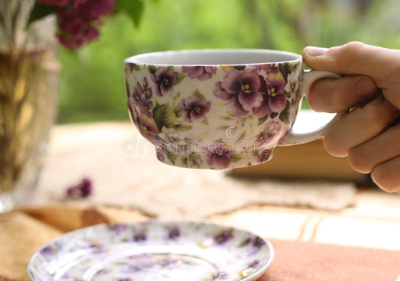 Hand hold cup of tea with lilac bouquet in vase and book stock photos
