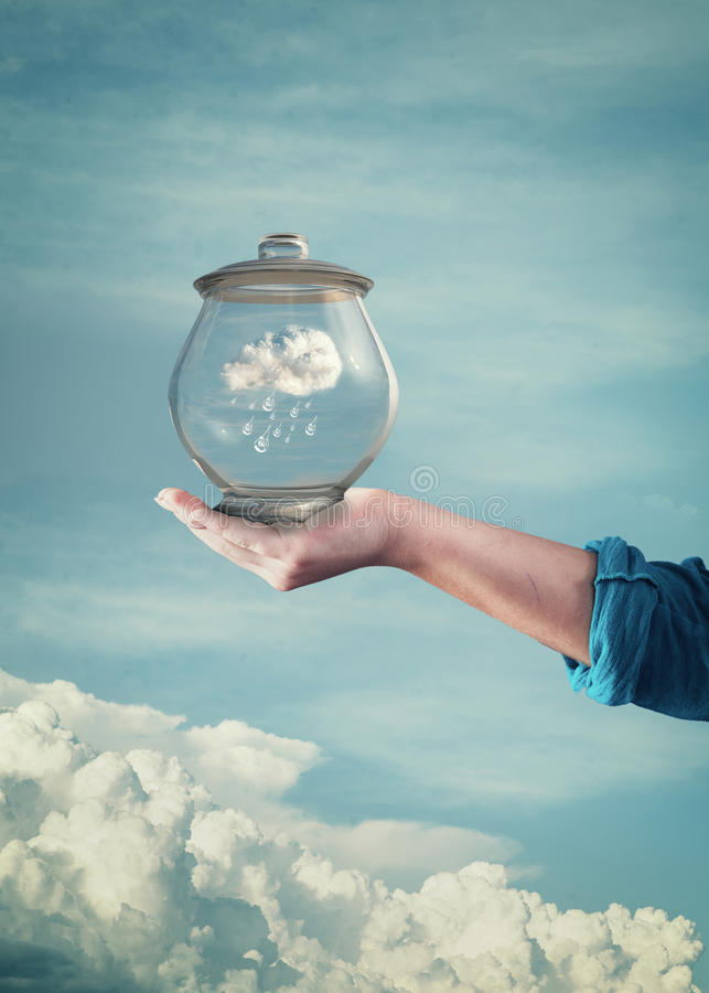 Hand hold glass jar with blue sky and clouds inside stock photo