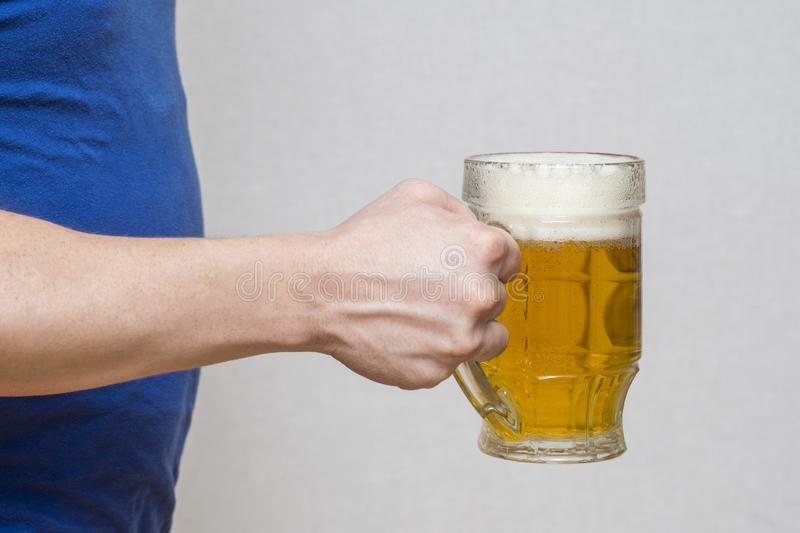 Hand hold glass mug of beer on white background. Beer in a glass holding by hand stock photography