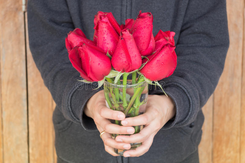 Hand hold glass of red rose. Stock photo stock photos