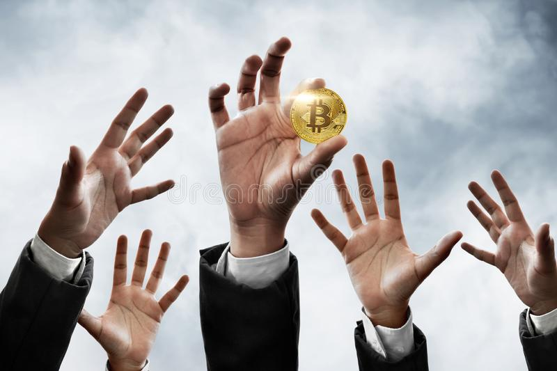 Hand holding golden bitcoin on sky background. Hand hold golden bitcoin on sky background royalty free stock photography