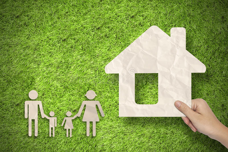 Hand hold House and family concept on green grass. Background royalty free stock image