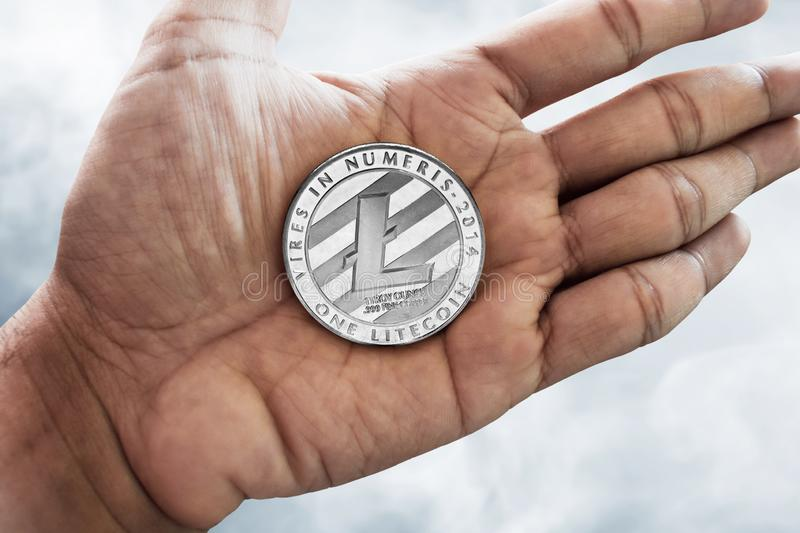 Hand holding litecoin on smoke background. Hand hold litecoin on smoke background royalty free stock images