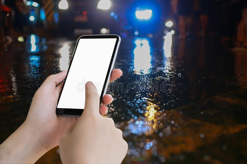Hand hold mobile blank screen and water on street and color. Lighting, traffic night illuminated reflection liquid,using the car on the road when it weather stock images