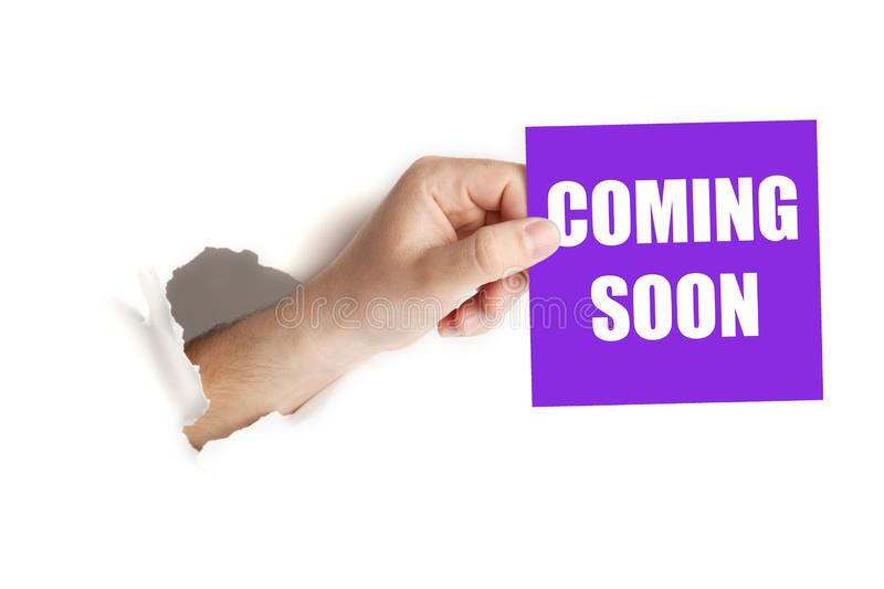 Hand hold paper with coming soon. Announcement of launch royalty free stock photo