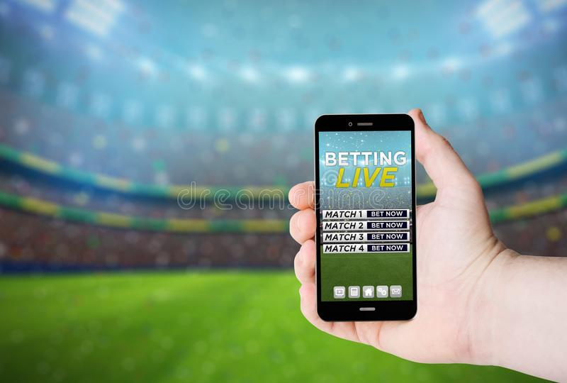 Hand hold a phone with betting online on a screen royalty free stock image
