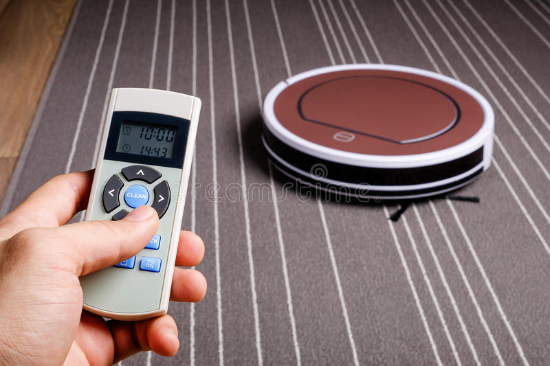 Hand hold remote control for robotic vacuum cleaner. On grey carpet smart cleaning technology stock photos