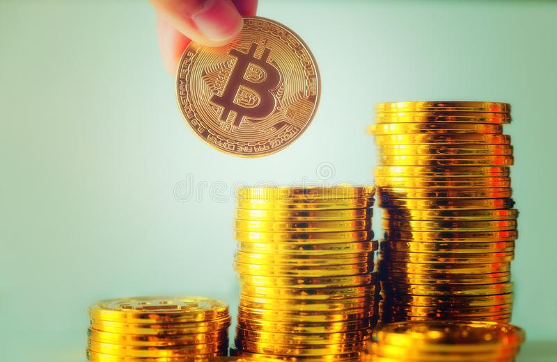 Hand hold a single bitcoin over Stack of glod bitcoins, Cryptocurrency concept. Virtual currency digital payment system royalty free stock photos