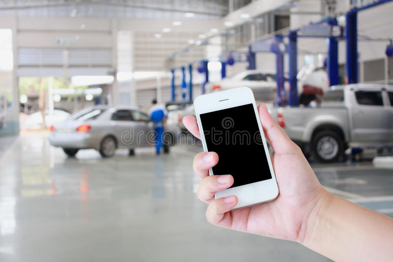 Hand hold smartphone with car repair service centre stock image