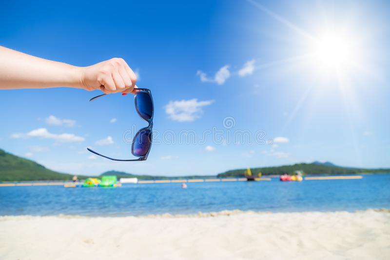 Hand hold sunglasses with sandy beach royalty free stock photo