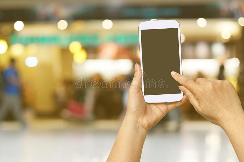 Hand hold and touch screen with Blur shopping mall. Background royalty free stock images
