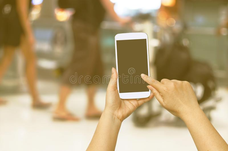 Hand hold and touch screen with Blur shopping mall. Background royalty free stock photos