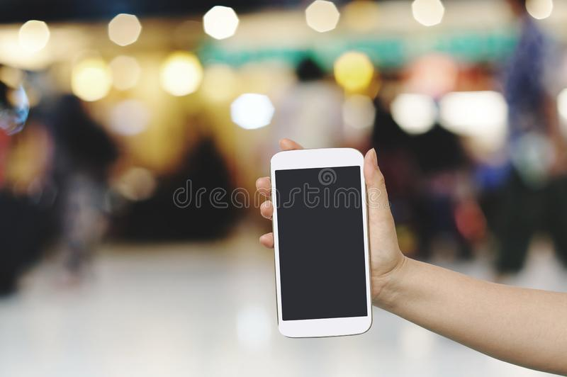 Hand hold and touch screen with Blur shopping mall. Background stock photos