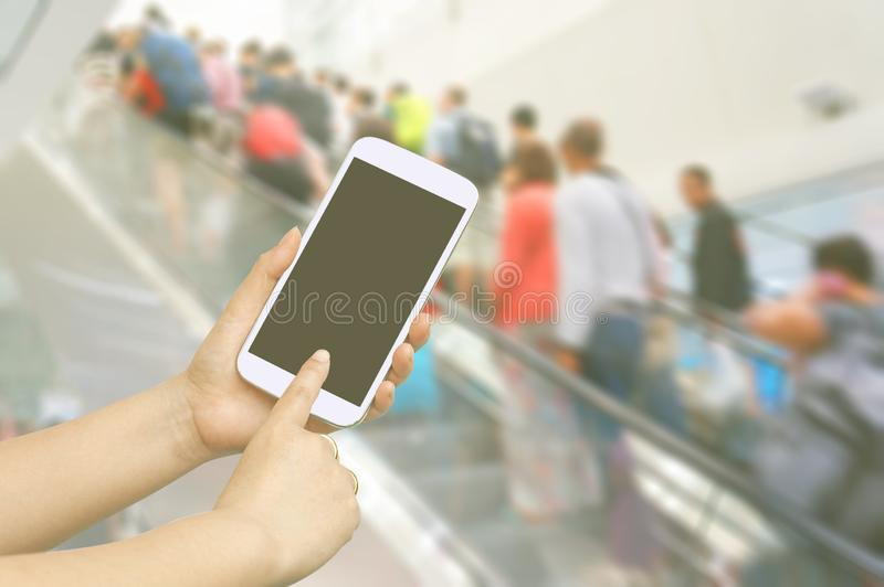 Hand hold and touch screen with people are going up the escalator in the Airport. Blur stock photography