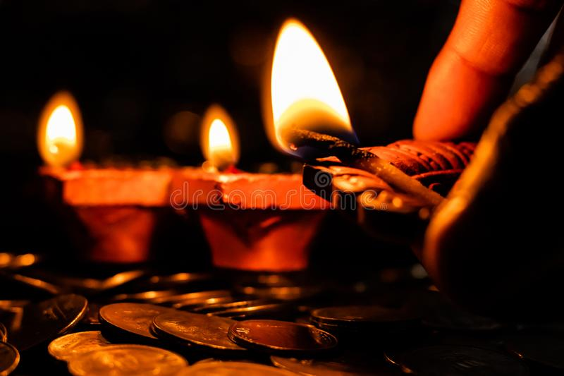 Hand holdin an earthen lamp to light other lamps on a pile of coins for Diwali decoration. Prosperity and hope concept royalty free stock photo