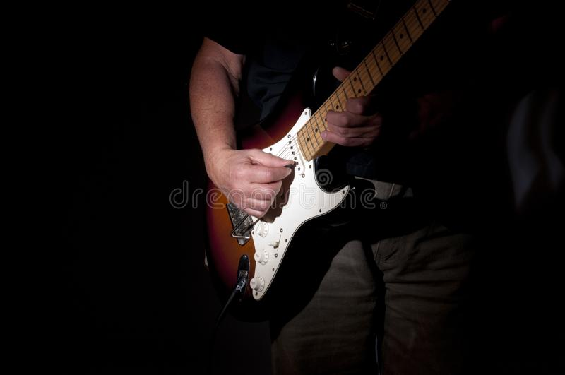 A hand holding a guitar. A hand holding an accoustic guitar stock photos