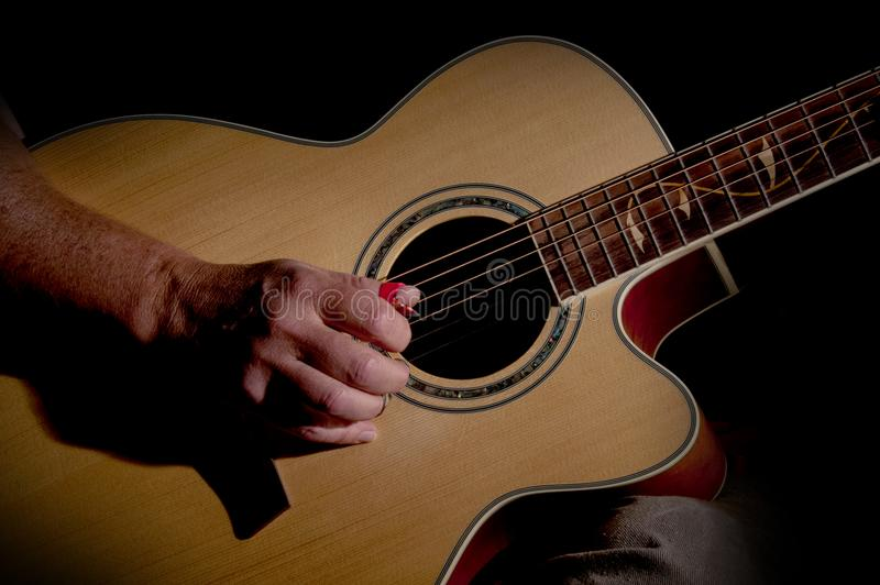 A hand holding a guitar. A hand holding an accoustic guitar stock images
