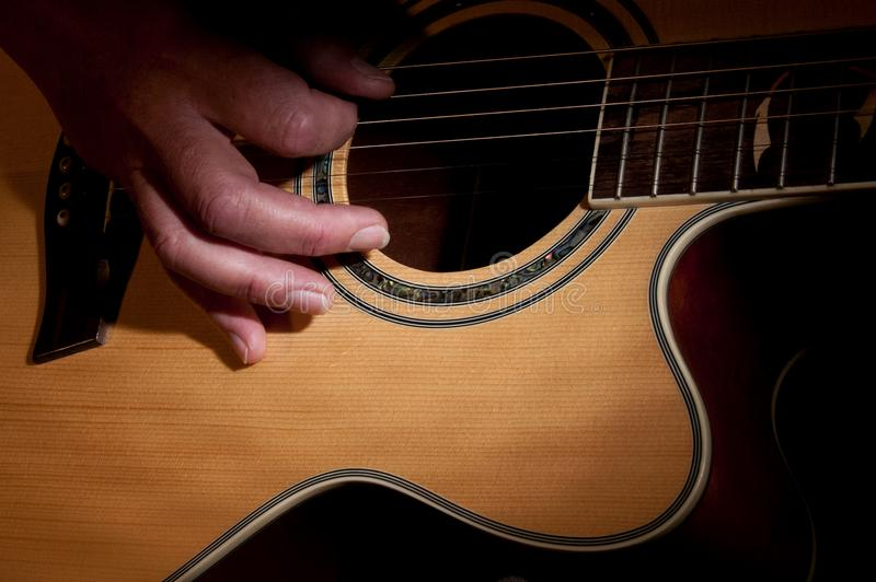 A hand holding a guitar. A hand holding an accoustic guitar royalty free stock photography