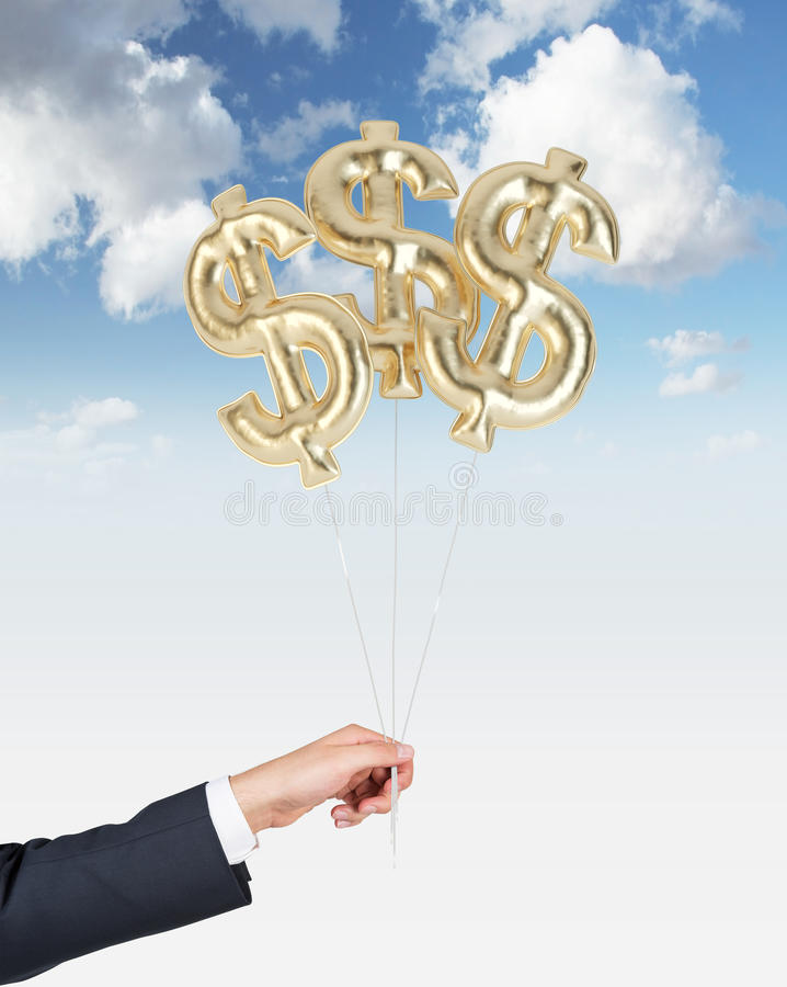 A hand is holding air balloons in a form of golden dollar signs. stock photo