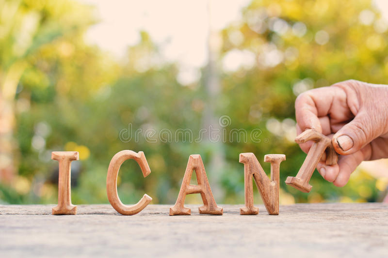 Hand holding alphabet wood. `I can` word on tree bokeh background stock photo