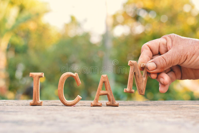 Hand holding alphabet wood. `I can` word on tree bokeh background royalty free stock photography
