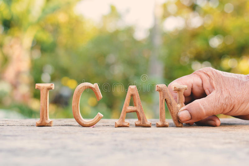 Hand holding alphabet wood. `I can` word on tree bokeh background royalty free stock photos