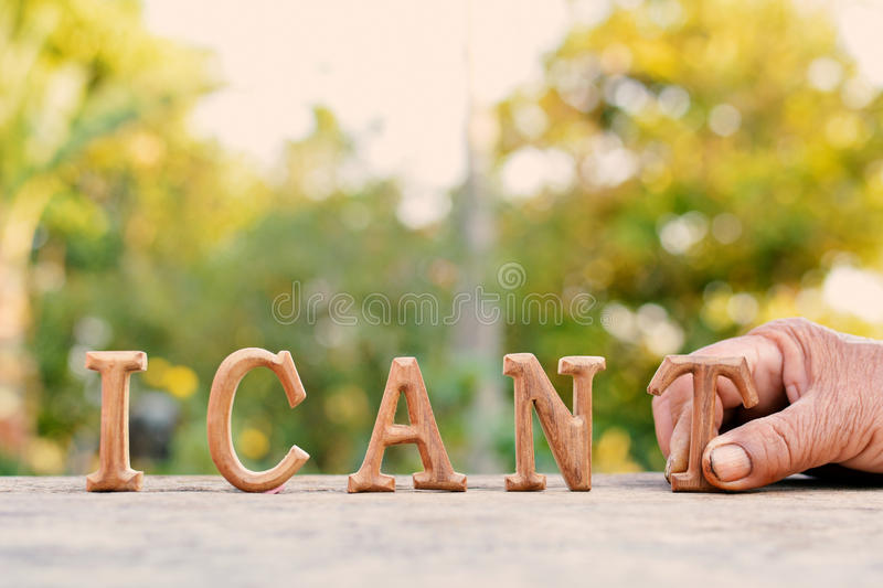 Hand holding alphabet wood. `I can` word on tree bokeh background royalty free stock photo
