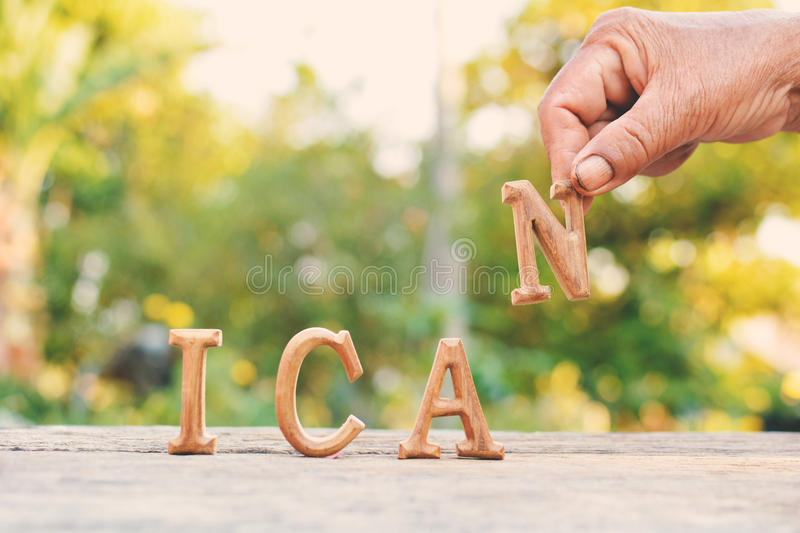 Hand holding alphabet wood. `I can` word on tree bokeh background royalty free stock images