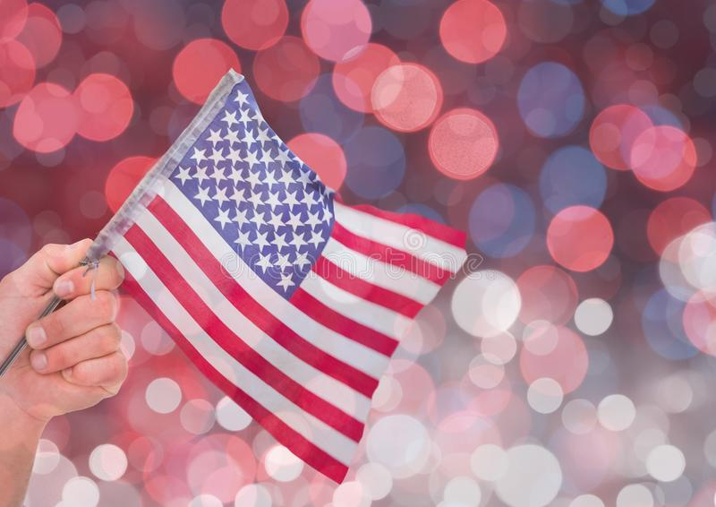 Hand holding American flag with sparkling light bokeh background. Digital composite of Hand holding American flag with sparkling light bokeh background royalty free stock photography