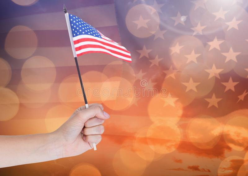 Hand holding American flag with sparkling light bokeh background. Digital composite of Hand holding American flag with sparkling light bokeh background royalty free stock image