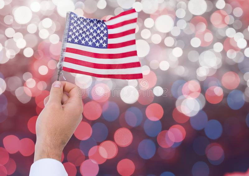 Hand holding American flag with sparkling light bokeh background. Digital composite of Hand holding American flag with sparkling light bokeh background royalty free stock photo