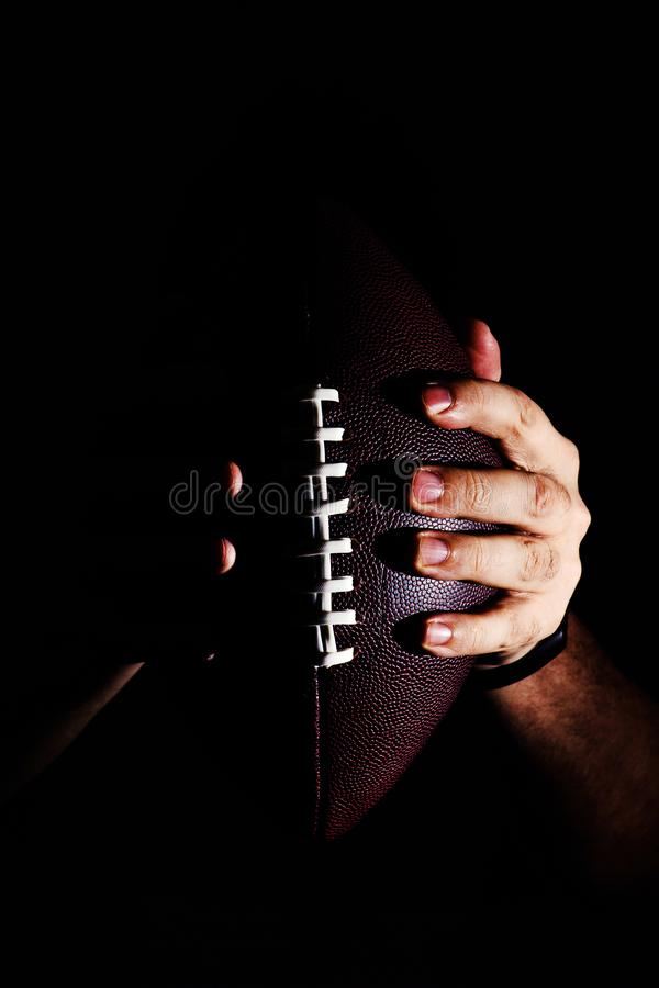 Hand holding American football ball isolated on black background. Activity, brown, closeup, college, competition, energy, equipment, game, lace, leather, nfl stock photo