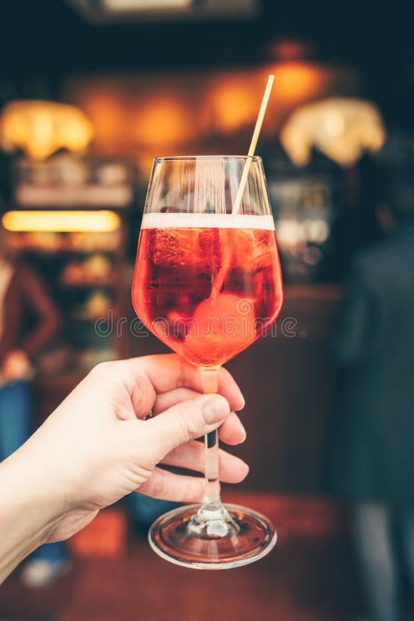 Hand holding aperol spritz. Woman`s hand holding typical italian coctail in wineglass - aperol spritz royalty free stock images