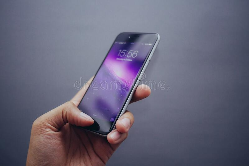 Hand holding Apple iPhone stock photo