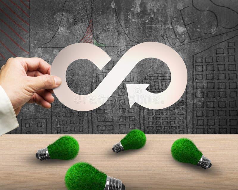 Hand holding arrow infinity recycling symbol, grass bulbs, circular economy. Circular economy and green energy concept. Man`s hand holding metal arrow infinity royalty free stock image