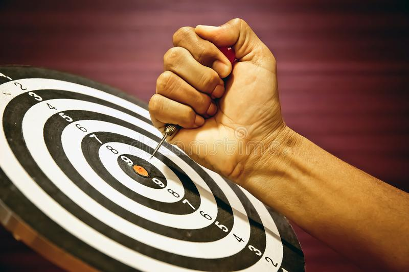 Hand Holding the arrow to dartboard center for Business focus. stock images
