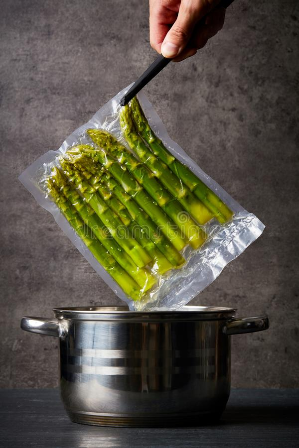Hand holding asparagus over cooking pot. Hand holding fresh asparagus in sous vide bag over cooking pot royalty free stock photo