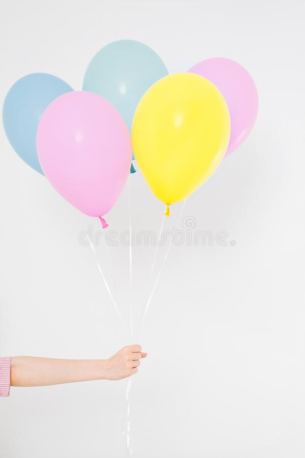 Hand holding balloons. Holiday concept. Colorful party balloons background. Isolated on white. Copy space royalty free stock photo