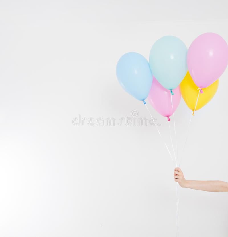 Hand holding balloons. Holiday concept. Colorful party balloons background. Isolated on white. Copy space stock image
