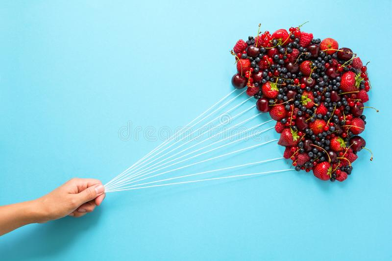 Hand holding balloons made of berries on blue paper background. Healthy eating concept. Flat lay stock images