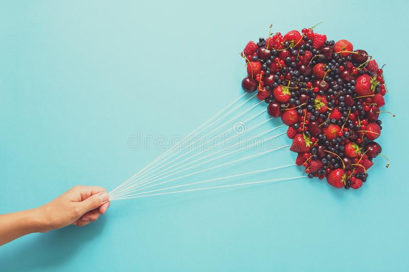 Hand holding balloons made of berries on blue paper background. Healthy eating concept. Flat lay. Toned.  royalty free stock photo