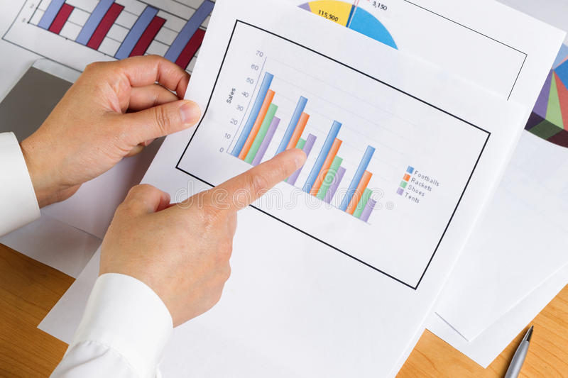 Hand holding bar chart graph while looking at financial data royalty free stock photography