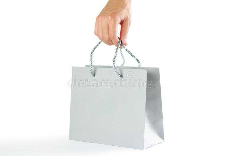 Hand holding beautiful gift gray bag. Close up. Isolated on white background. stock images