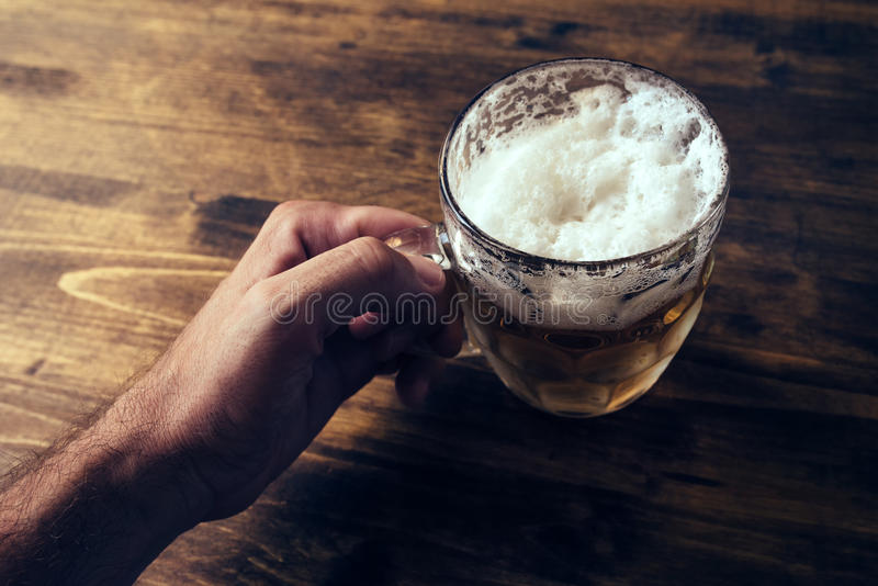 Hand holding beer mug full of cold fresh alcohol drink stock photo