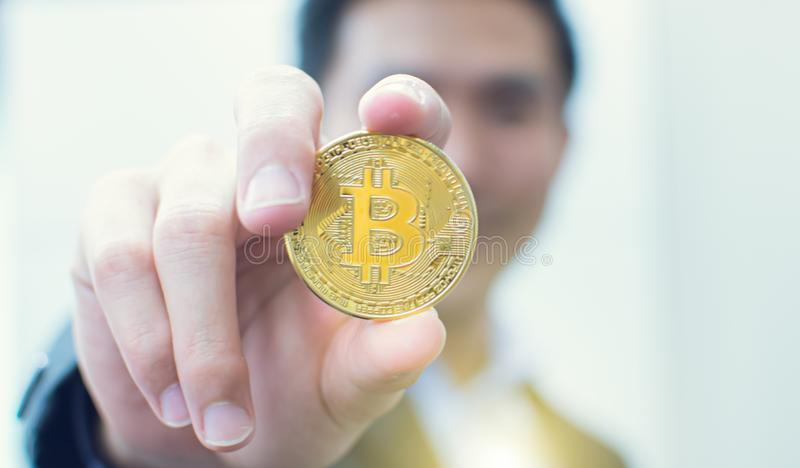 Hand holding bitcoin with blur background of business man royalty free stock image