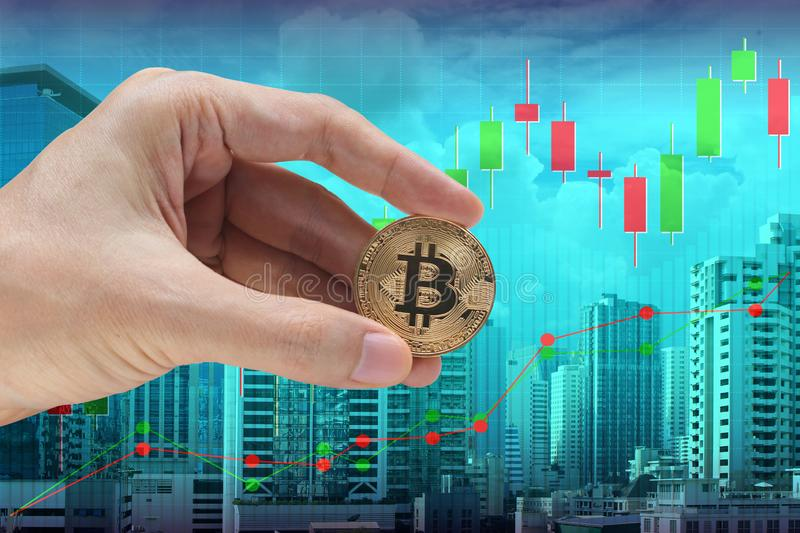 Hand holding the bitcoin with cityscape and stock market or financial graph for financial investment concept.  royalty free stock images
