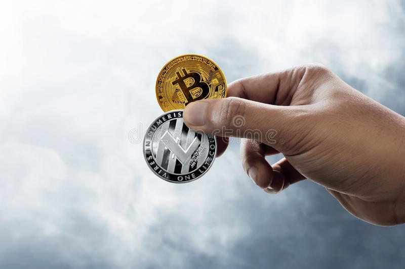 Hand holding bitcoin and litecoin coins. Hand hold bitcoin and litecoin coins stock photo
