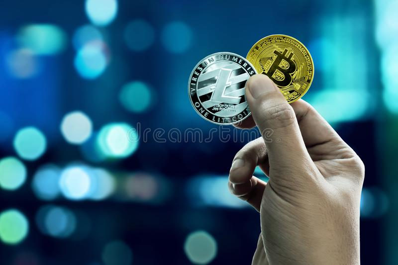 Hand holding bitcoin and litecoin coins. Hand hold bitcoin and litecoin coins stock images